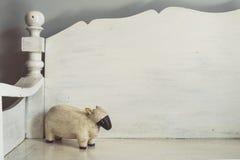 Tono del vintage de la muñeca de madera linda de las ovejas en el banco de madera Imagenes de archivo