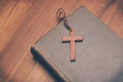 Tono del vintage del collar cruzado cristiano de madera en la Sagrada Biblia Imágenes de archivo libres de regalías