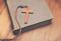 Tono del vintage del collar cruzado cristiano de madera en la Sagrada Biblia Imagen de archivo libre de regalías