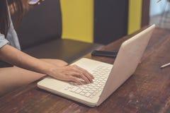 Tono del vintage Una mujer está trabajando usando el ordenador portátil en la tabla S Imagen de archivo
