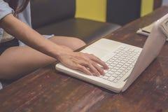 Tono del vintage Una mujer está trabajando usando el ordenador portátil en la tabla S Foto de archivo libre de regalías