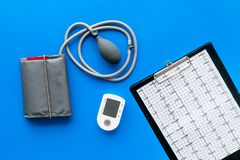 Tonometer and cardiogram for heart diseases diagnostic on blue background top view. Tonometer cardiogram for heart diseases diagnostic on blue desk background stock photos