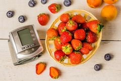 Tonometer, heart rate monitor to measure the body basket of strawberries on a white wooden vintage table blueberries and apricots. Stock Images