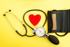 Tonometer for measuring blood pressure with the concept of a healthy stethoscope and red heart on a yellow background. stock image