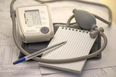 Tonometer和笔记本有钢笔的在医疗图表和诊断,地方背景文本的 库存照片