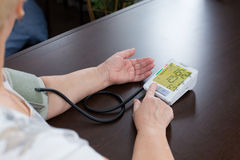Tonometer in the woman's hands. The woman measures to herself a blood pressure Stock Images