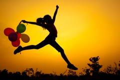 Tonårig flicka med ballonger som hoppar på naturen Royaltyfri Fotografi