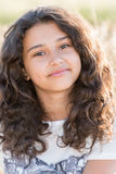 Tonårig flicka med lockigt mörkt hår på naturen Royaltyfria Bilder