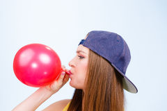 Tonårig flicka som blåser den röda ballongen Fotografering för Bildbyråer