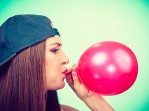 Tonårig flicka som blåser den röda ballongen Arkivbilder