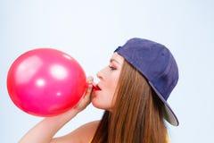 Tonårig flicka som blåser den röda ballongen Royaltyfri Foto