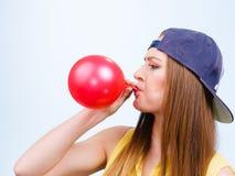 Tonårig flicka som blåser den röda ballongen Arkivbild