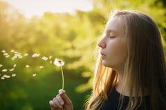 Tonårig flicka som blåser maskrosen i solnedgångljus Royaltyfria Foton