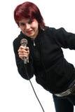 Tonårig flicka som sjunger med en mikrofon Fotografering för Bildbyråer