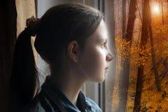Tonårig flicka som ut ser fönstret Royaltyfri Foto