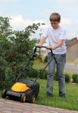 Tonårig hjälp mejar gräsmattan Royaltyfria Bilder