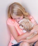 Tonårig krama hund i hörn Arkivbilder