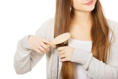Tonårig kvinna som borstar hennes hår Arkivbild