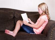 Tonårig läsning en bok Royaltyfria Bilder