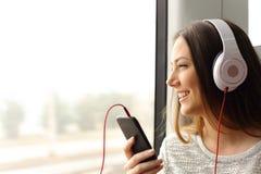 Tonårig passagerare som lyssnar till musikresanden i ett drev Arkivbild
