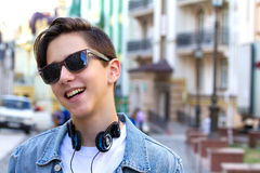 Tonårig pojke med musikhörlurar i stads- bakgrund Royaltyfri Bild