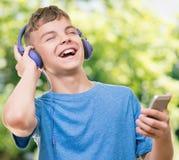 Tonårig pojke med telefonen Arkivfoto