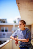 Tonårig pojkebenägenhet på balkongstången på Sunny Day Arkivfoton