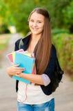 Tonårig studentflicka med böcker och en ryggsäck i händer Arkivfoton
