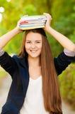 Tonåriga böcker för studentflickainnehav Royaltyfria Foton
