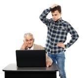 Tonårigt med hans farfar på bärbara datorn Arkivfoto