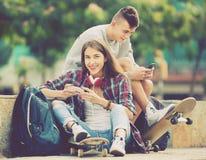 Tonåring och hans flickvän med smartphones Arkivfoto