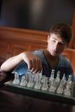 Tonåring som är tänkande av hans strategi Arkivfoto