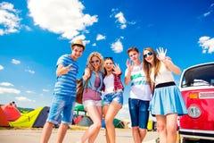 Tonåringar på sommarmusikfestivalen vid rött campervan för tappning Royaltyfri Bild