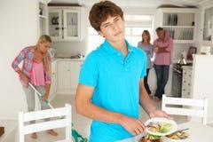 Tonåringar som gör motvilligt hushållsarbete Arkivbild