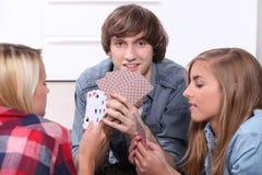 Tonåringar som leker kort Royaltyfri Foto