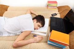 Tonåringen sover, når han har lärt Arkivfoton