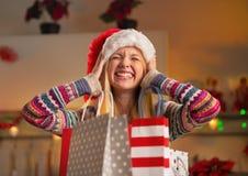 Tonåringflicka i den santa hatten med shoppingpåsar Arkivbild