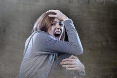 Tonåringflicka med rött hår som känner ensamt skrikigt desperat a Arkivfoto