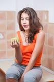 Tonårs- flicka i den orange t-skjortan som ser ett grönt äpple Royaltyfri Bild