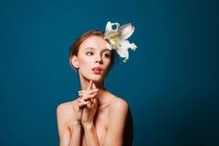 Tonårs- flicka med den vita blomman på blått Fotografering för Bildbyråer