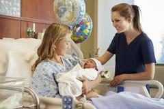 Tonårs- flicka med sjuksköterskan Holding Newborn Baby i sjukhus Royaltyfria Bilder