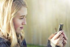 Tonårs- flicka som använder en mobiltelefon Arkivfoton