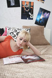 Tonårs- flicka som ser tidskriften i säng Arkivfoton