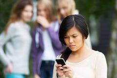 Tonårs- flicka som trakasseras av textmeddelandet på mobiltelefonen Royaltyfri Bild