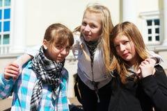 Tonårs- flickor mot en skolabyggnad Arkivfoton