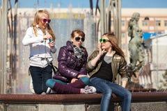 Tonårs- flickor som kopplar av mot en stadsspringbrunn Royaltyfri Bild