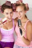 Tonårs- flickor som sjunger in i hårborstar Royaltyfri Foto