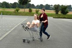 Tonårs- flickvänner med shoppingvagnen Royaltyfri Bild