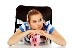 Tonårs- kvinna med piggybank på tabellen Arkivbilder