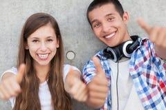 Tonårs- par med tum upp Arkivbild